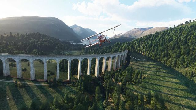 A red biplane flied over a rustic train trestle bridge in rural Britain.