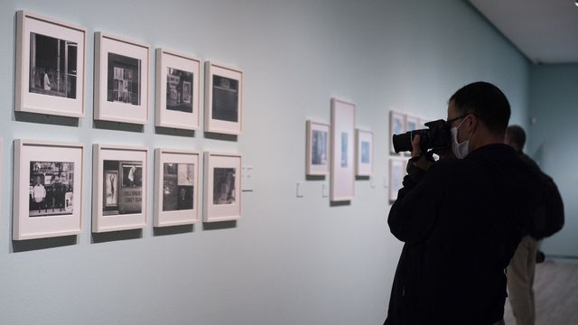 a person takes a photo of eight photographs on the wall at an art gallery