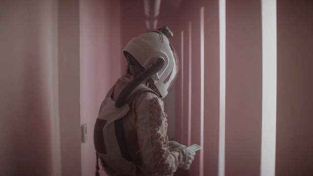 """A space-suited """"knocker"""" in a long pink hallway full of bright white lights in the science fiction movie Doors"""