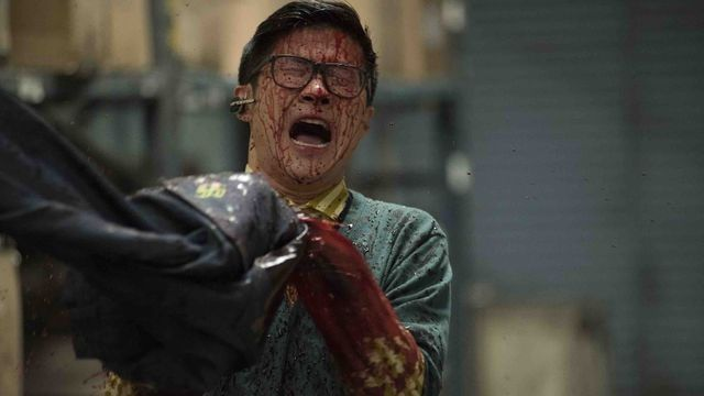 A bloodied man in glasses screams as he holds onto a pair of jeans that might be eating his arm maybe?