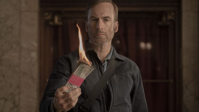 Bob Odenkirk lights a stack of hundred dollar bills in Nobody