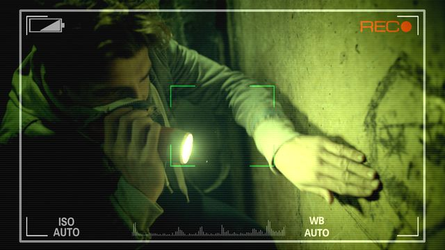 "A man seen through a camera lens, with a red ""REC"" on the screen indicating he's being recorded, points a camera at a wall in a dark room in Deadhouse Dark"
