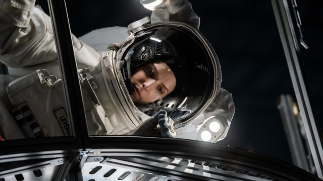 Anna Kendrick, in a space suit, hovers sideways over a grate in Stowaway