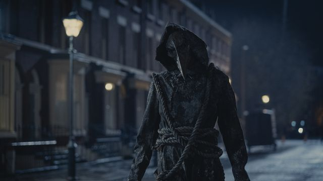 A ghostly plague doctor haunts the streets of London at night in The Irregulars