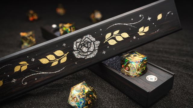 An elegant inlaid flower and leaf pattern, rendered in flecks of silver and gold, sit above two creamy, sharp-edged dice to match.