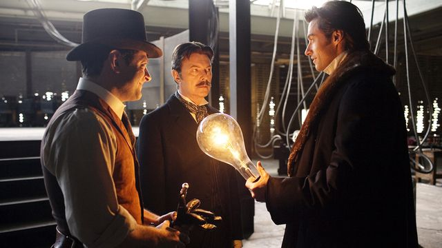Robert Angiers (Hugh Jackman) holds a glowing bulb beside Nikola Tesla (David Bowie) and his assistant Alley (Andy Serkis)