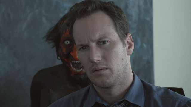 A red-faced demon tauntingly scowls over the shoulder of Josh Lambert (Patrick Wilson) in James Wan's Insidious