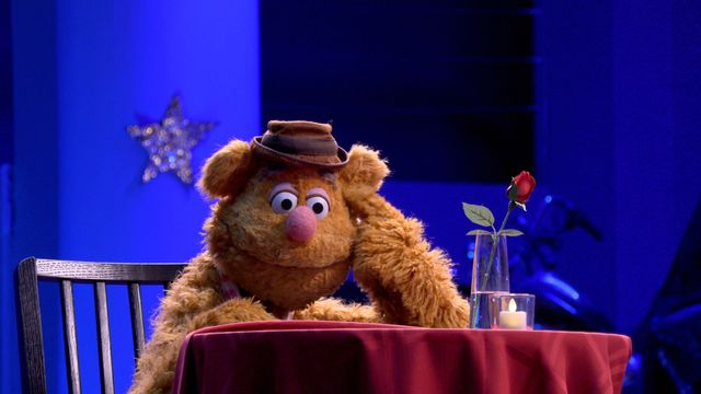 Fozzy Bear sits dejected at a restaurant table in the Muppets Now! premiere.
