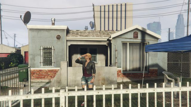 Grand Theft Auto Online - a blonde woman in jean shorts and a leather jacket facepalms. She is standing in front of a blue and brick house.