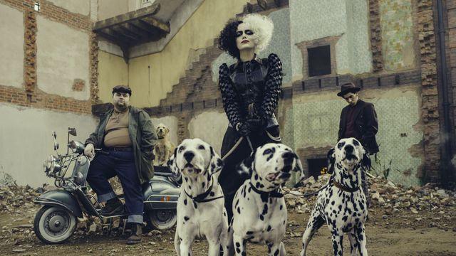 Cruella (Emma Stone) holding three Dalmatians on a leash