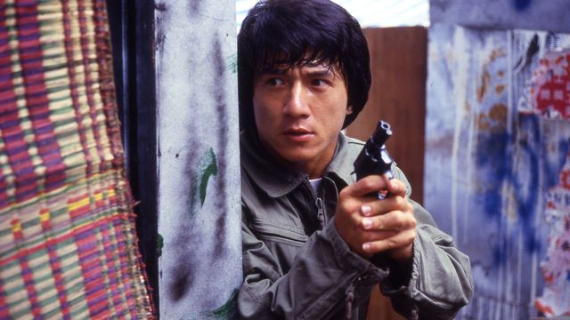 Jackie Chan as police inspector Chan Ka-Kui holds a revolver as he peers around a corner in Police Story
