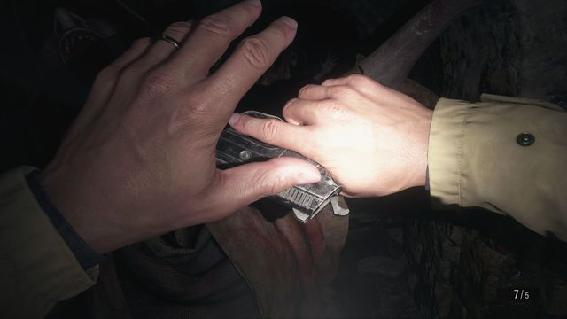 Ethan Winters holds up his hands to guard against an enemy in Resident Evil Village