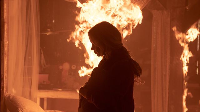 Evelyn, holding her daughter in front of flames, in A Quiet Place Part II
