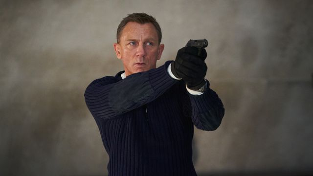 james bond holds his pistol while wearing a blue sweater