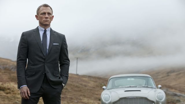 Daniel Craig as James Bond standing in front of a car in Skyfall