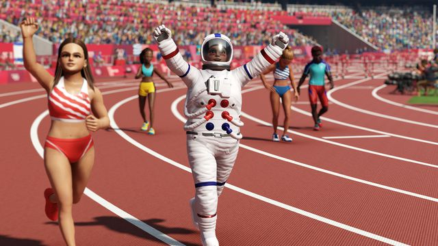 An astronaut raises their arms after finishing second behind a traditionally-dressed track-and-field athlete