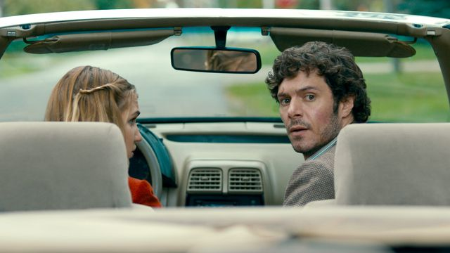Adam Brody as P.I. Abe Applebaum looks behind himself from the passenger seat of Gracie Gulliver's (Kaitlyn Chalmers-Rizzato) car in The Kid Detective