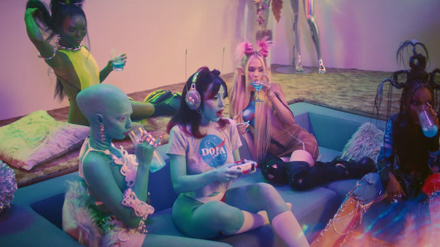 Doja Cat sits in a futuristic midcentury style sunken living room while holding on a playstation 5 controller. she's surrounded by a ton of alien girls