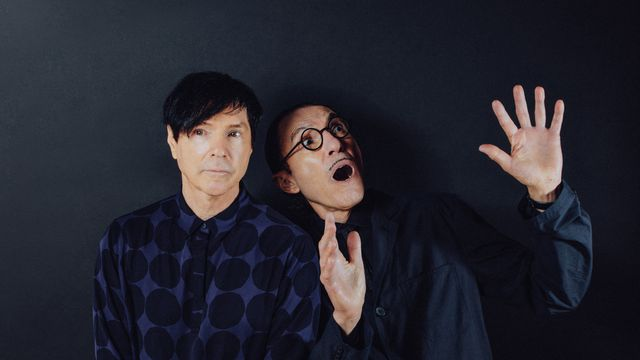 Russell and Ron Mael, in dark blue against a near identical dark blue background, mug for the camera in The Sparks Brothers