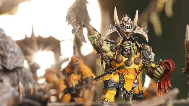 Warhammer Fantasy - a war boss orc model, holding a gilded helmet and holding his ax in the air.