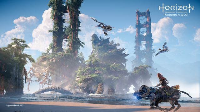 Aloy riding a Charger on the beach past the ruins of the Golden Gate Bridge in Horizon Forbidden West