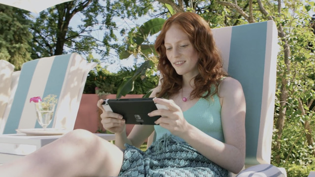 a young person sitting on a pool chair while playing their Nintendo Switch