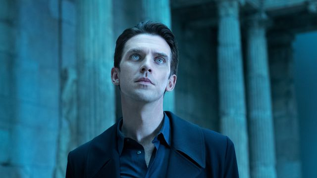 Dan Stevens, as the AI Tom in I'm Your Man, stands in a blue-lit columned ampitheater, looking upward