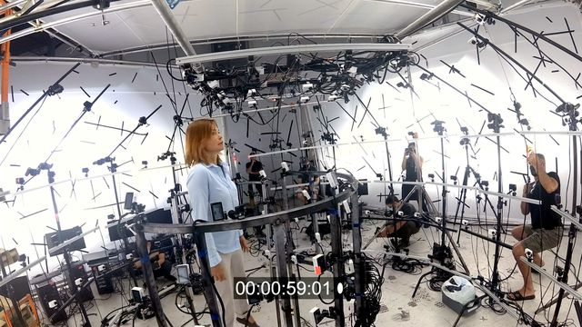 A behind-the-scenes shot from Neill Blomkamp's Demonic, with an actor standing under a dome rig covered with cameras